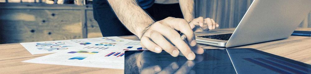 Ein Mann verwendet an einem Schreibtisch zeitgleich ein Notebook und ein Tablet.