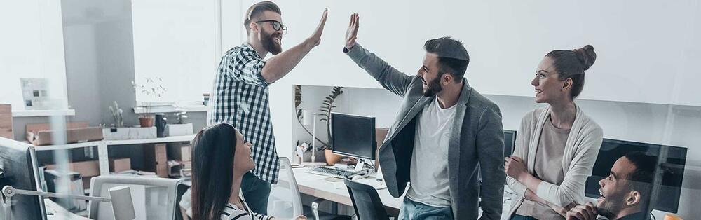 Eine Gruppe Personen unterhält sich ein einem Büro. Zwei Männer schlagen mit ihren Händen ein.