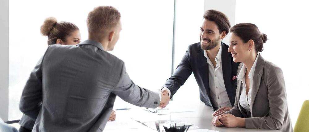 Eine Gruppe Personen sitzt sich gegenüber. Zwei Männer reichen sich die Hand.