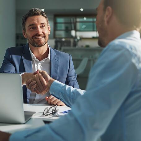 Zwei Männer reichen sich an einem Schreibtisch die Hand.