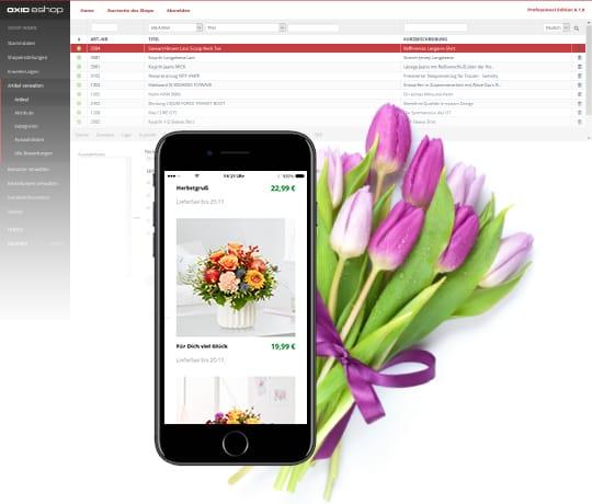 Das Backend der Enterprise Edition des OXID eShops. Im Vordergrund ist ein Smartphone mit einem geöffneten Shop.