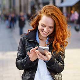 Eine Frau steht in einer Stadt und nutzt ihr Smartphone. Sie hat einen glücklichen Gesichtsausdruck.